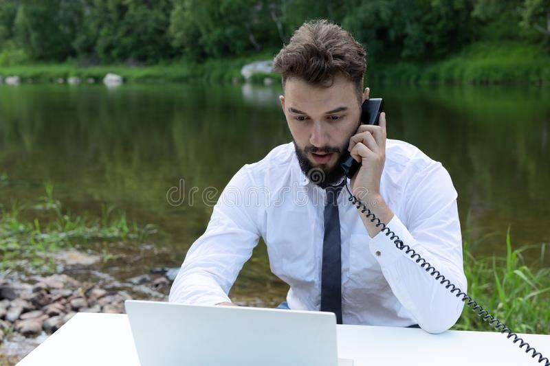 Young, bearded guy on worktable in summer, using laptop, talking on phone. man working, studying or surfing web in park royalty free stock photo