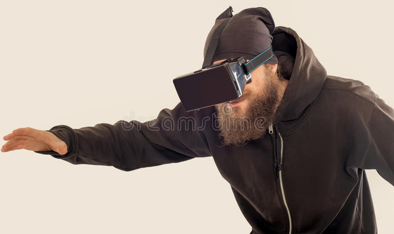 Young bearded handsome man using virtual reality device stock photo