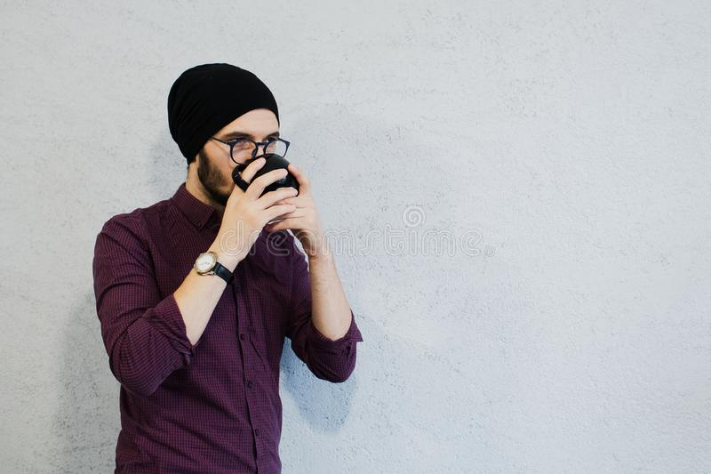 Young bearded hipster guy drink coffee, on white background. royalty free stock photography