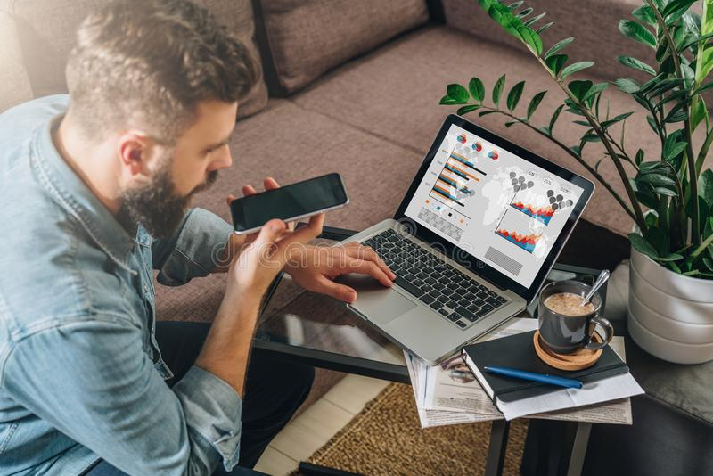 Young bearded hipster man, entrepreneur sits on couch at coffee table,uses laptop with graphs, charts on screen royalty free stock photo