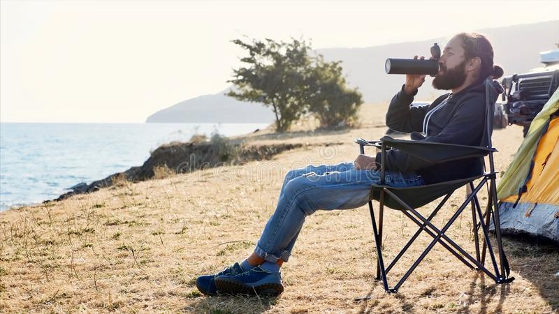 Young man sits on chair at campsite on lake shore and drinking from thermos. Young bearded hipster man sits on folding chair at campsite on lake shore and royalty free stock photos