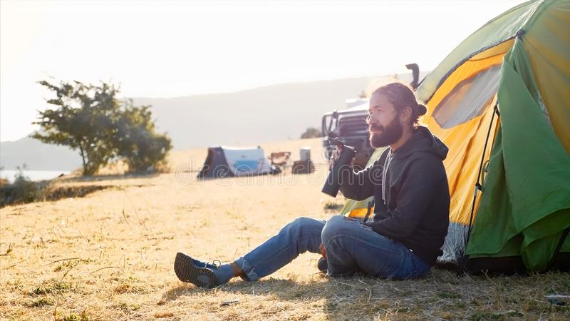 Young man sits on near the tent at campsite and drinking tea from thermos bottle. Young bearded hipster man sits on the ground next to touristic tent at royalty free stock photo