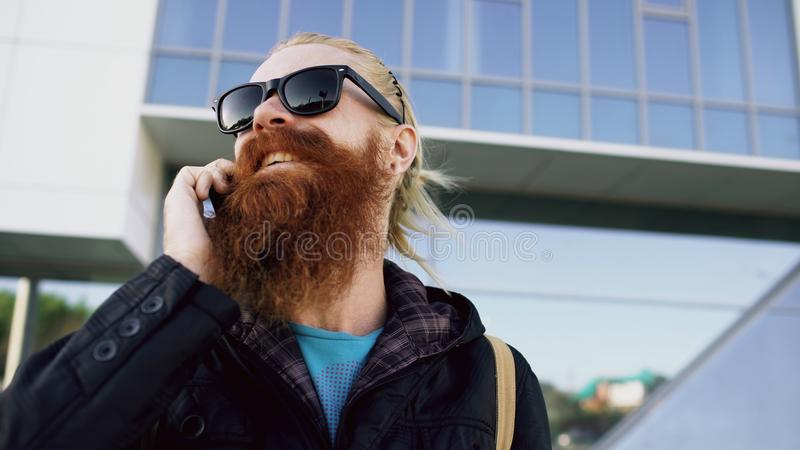 Closeup of Young bearded hipster man in sunglasses smiling and talking smartphone near office buildings stock photos