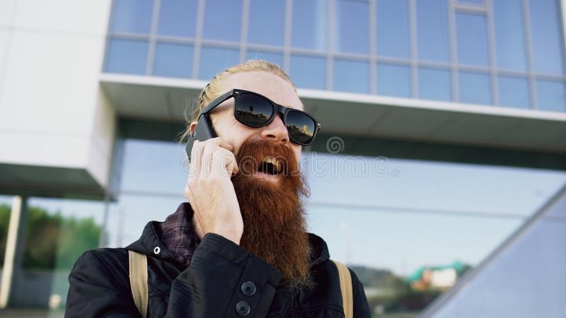 Closeup of Young bearded hipster man in sunglasses smiling and talking smartphone near office buildings stock photo