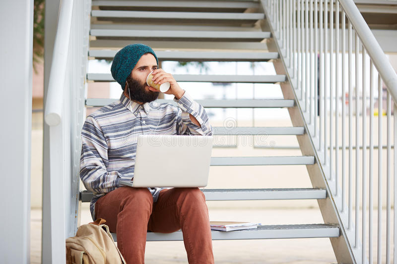 Young bearded hipster student using computer outdoors stock photo