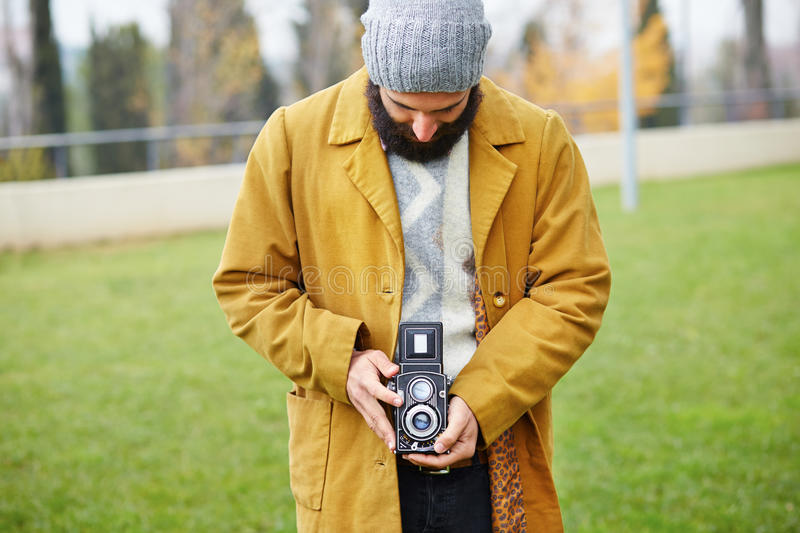Young bearded hipster taking photo with TLR camera royalty free stock images