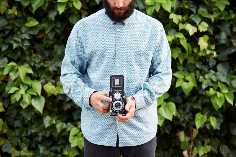 Young bearded hipster taking photo with TLR camera stock photography