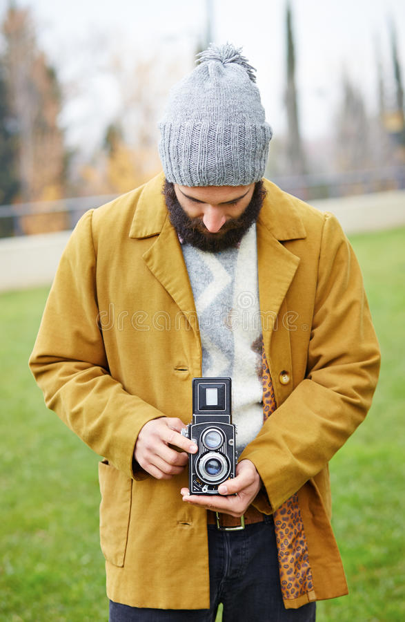 Young bearded hipster taking photo with TLR camera stock image