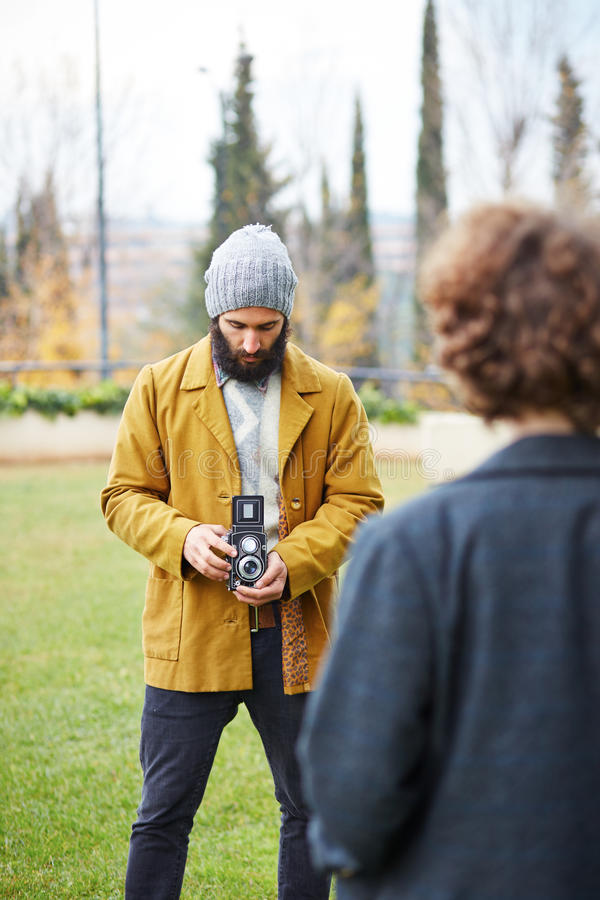 Young bearded hipster taking photo to redhead girl with TLR came royalty free stock image