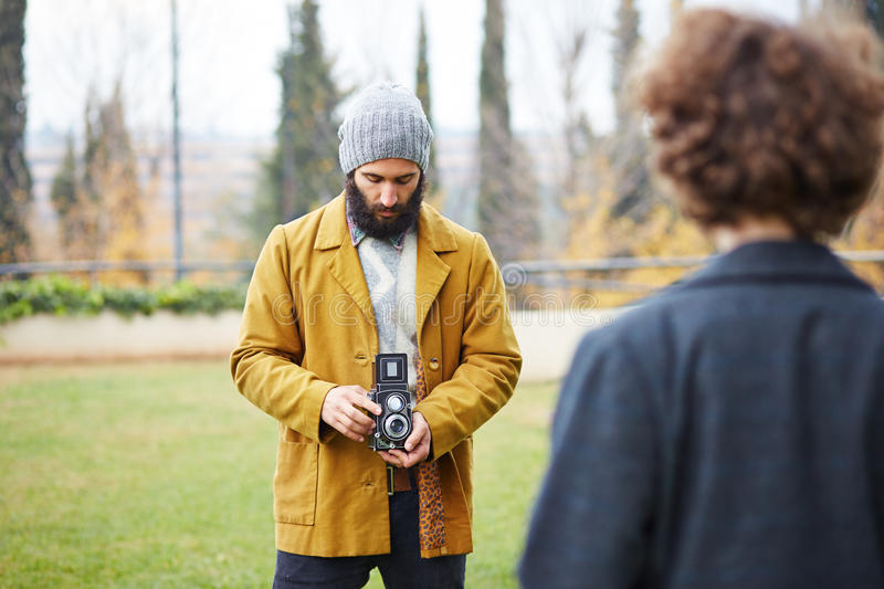 Young bearded hipster taking photo to redhead girl with TLR came royalty free stock photography