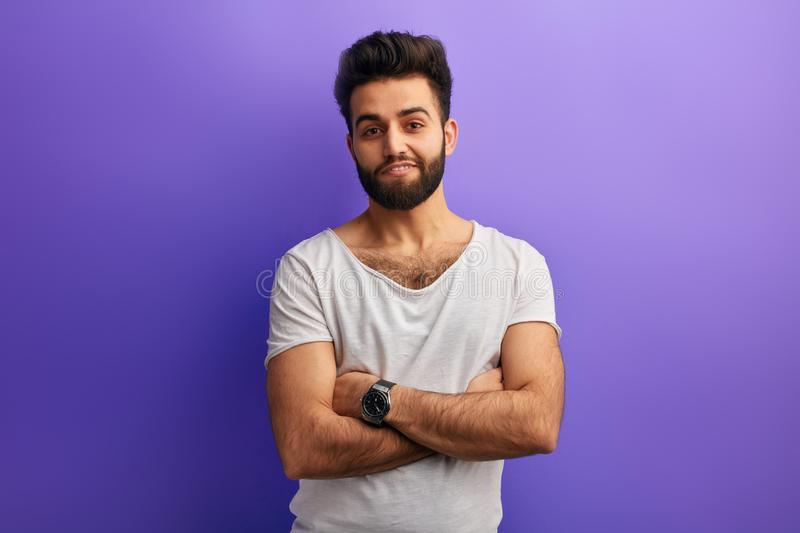 Young bearded Indian man standing with crossed arms against blue background royalty free stock images