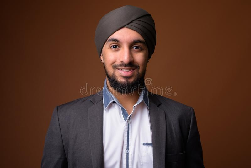 Young bearded Indian Sikh businessman wearing turban against bro royalty free stock image