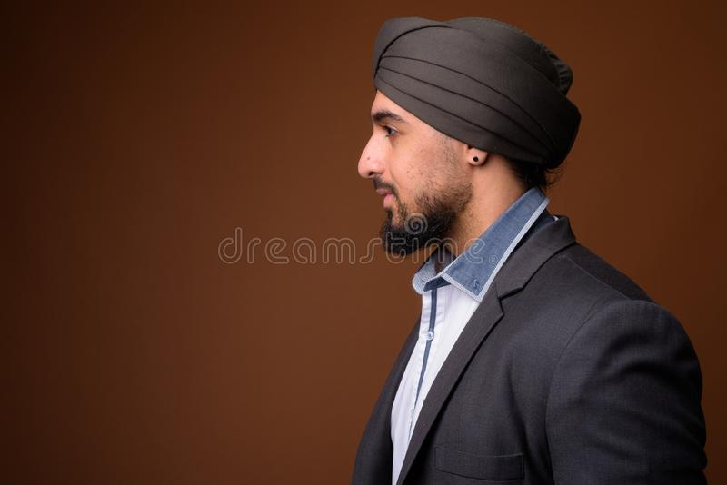 Young bearded Indian Sikh businessman wearing turban against bro stock image