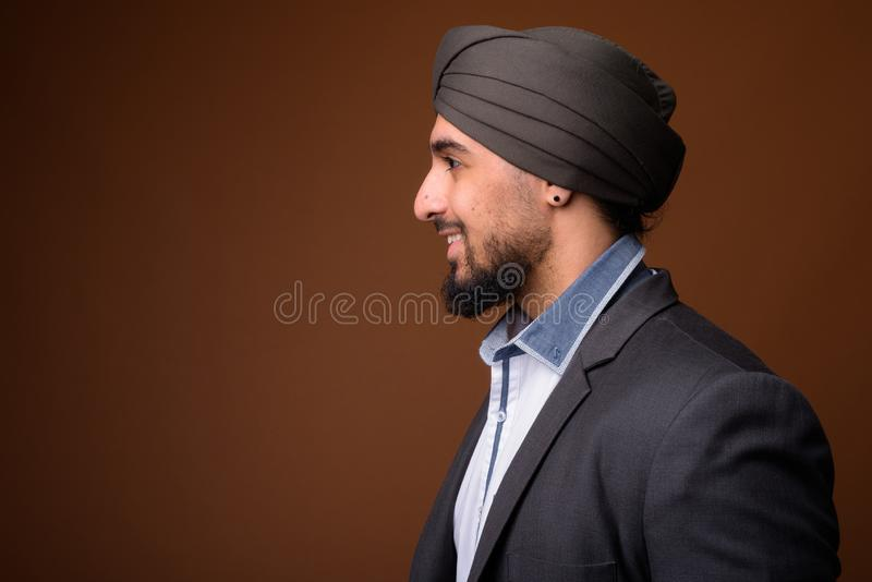 Young bearded Indian Sikh businessman wearing turban against bro stock photo