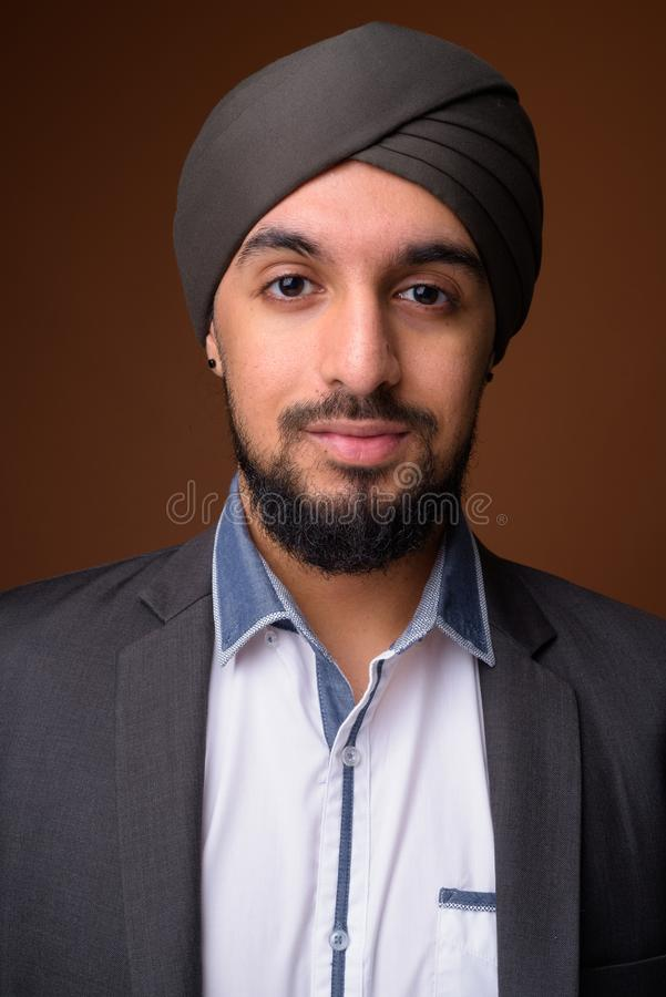 Young bearded Indian Sikh businessman wearing turban against bro royalty free stock photography