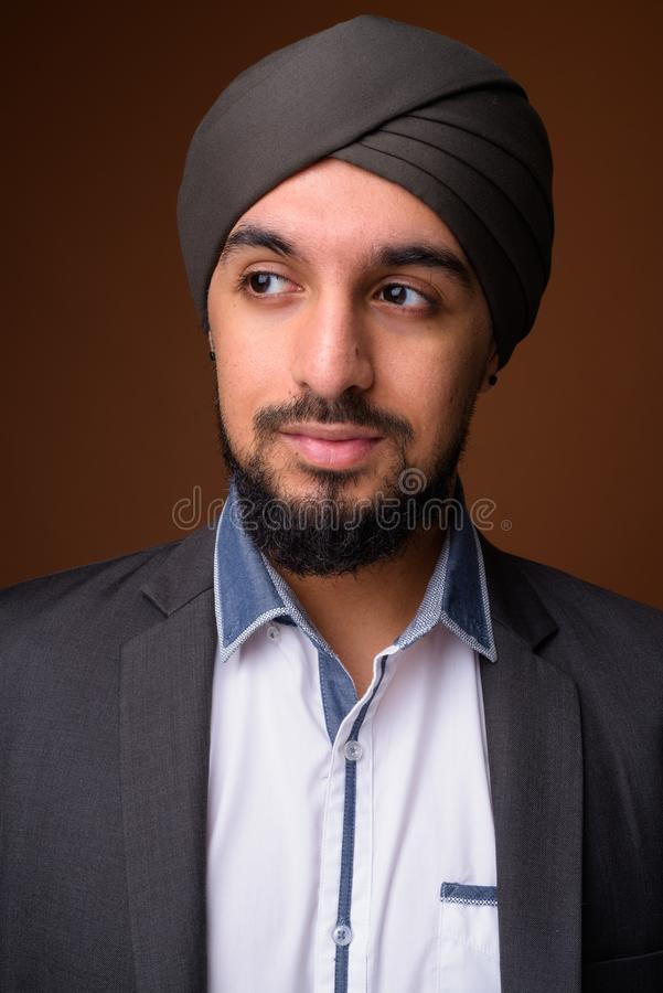 Young bearded Indian Sikh businessman wearing turban against bro stock images