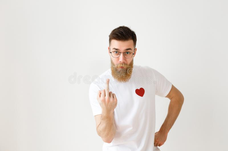 Young bearded male in eyewear, white casual t shirt with red heart, shows middle finger, expresses negativity, poses royalty free stock photo