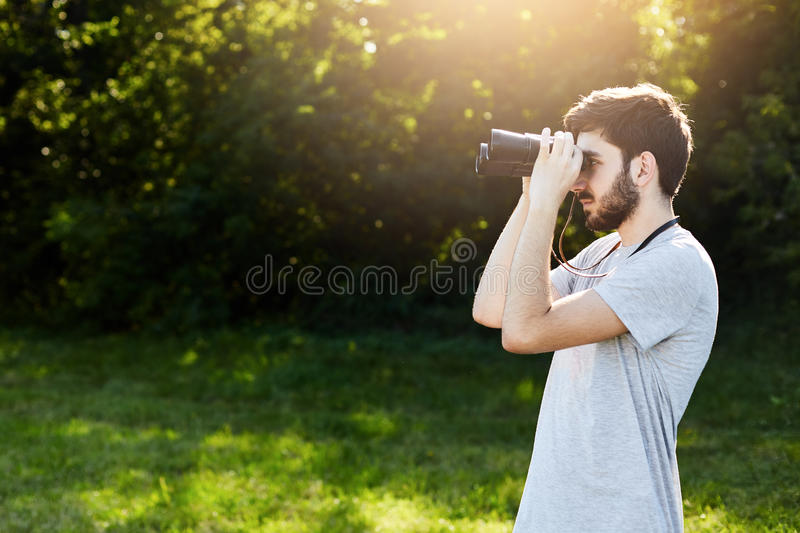 Young bearded male looking through binoculars while standing at green field, observing something. Handsome young guy having expedi. Tion across unknown places royalty free stock photos