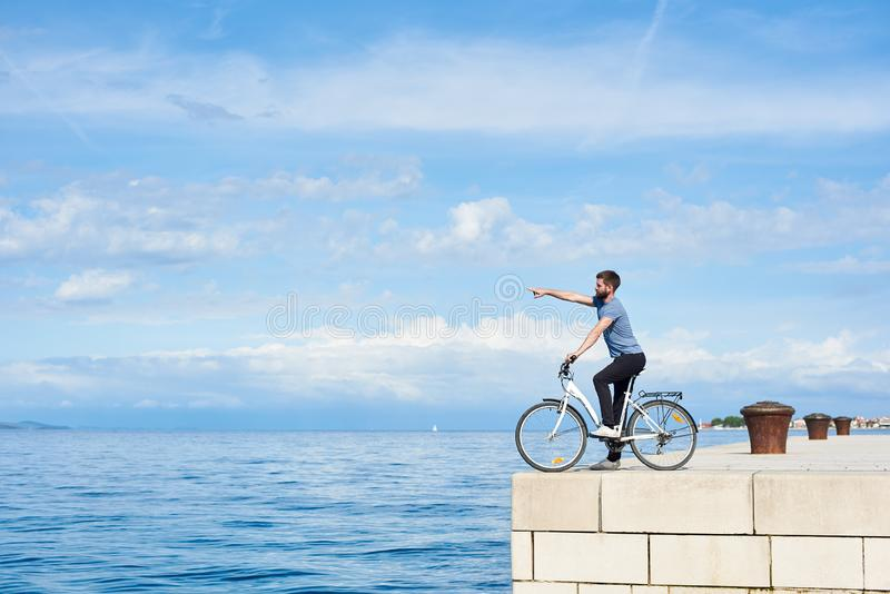 Young bearded man tourist on bicycle on high paved stone sidewalk enjoying clear blue sea water. Young bearded man on bicycle on high paved stone sidewalk stock image