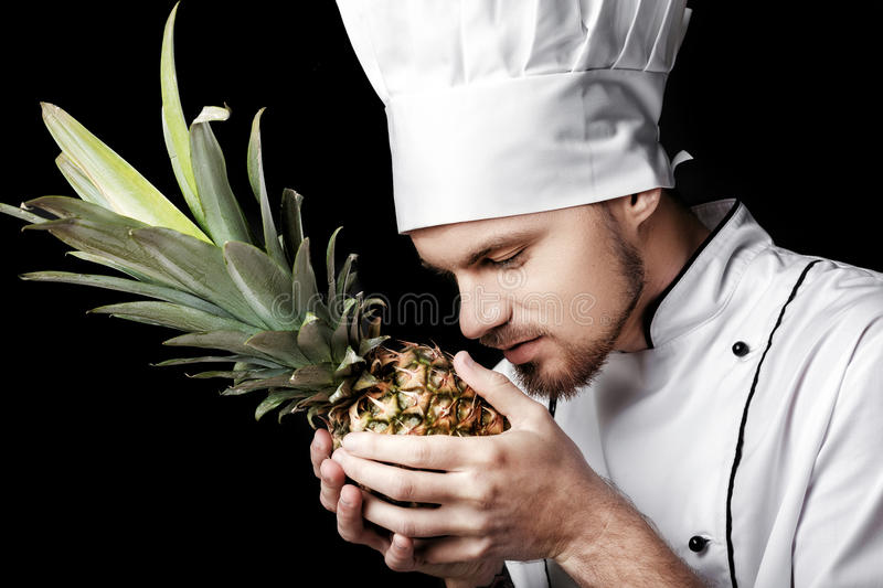 Young bearded man chef In white uniform holds Fresh pineapple on black background. Young bearded man chef In white uniform holds a Fresh pineapple on a black stock images