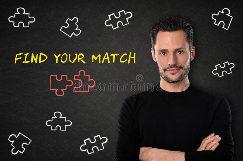 Young bearded man with crossed arms, puzzle pieces and text `Find your match` on a blackboard background. stock photography