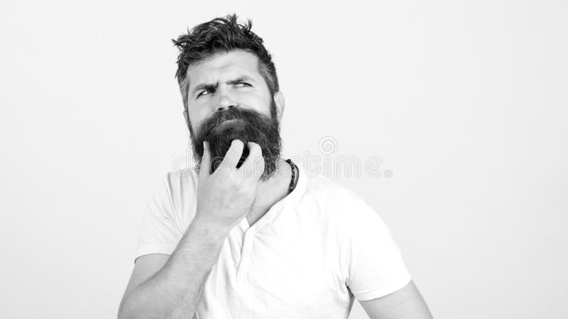 Young bearded man doubting, over white wall. Copy space. Handsome man thinking an idea. Man has own startup project idea stock photos