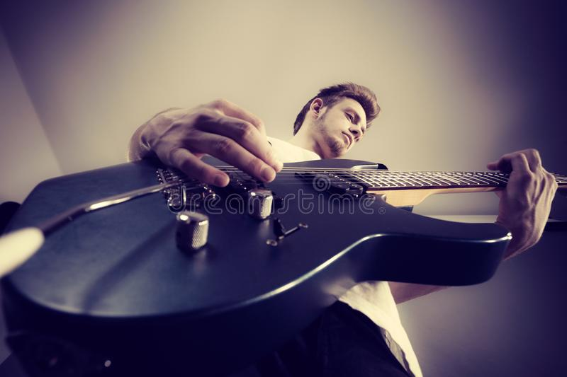 Young man playing electric guitar. Young bearded man with electric guitar. Adult person is holding instrument and playing. Hobby, music concept, unusual view stock image