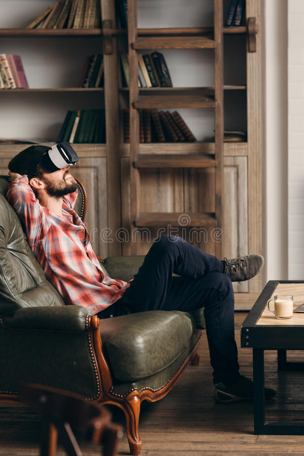 Young bearded man enjoying virtual reality glasses. Relaxed smiling guy in vr headset watching movie at home. Innovation, modern technology, rest, cyberspace royalty free stock photography