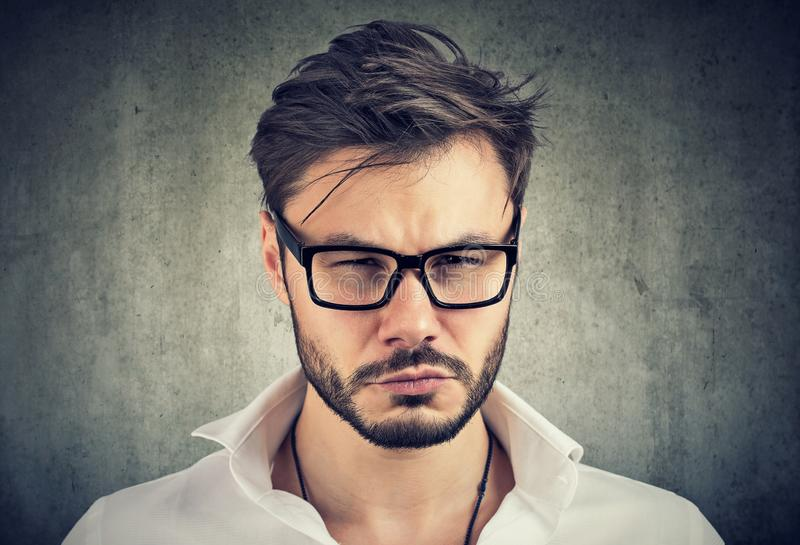 Envy man looking gloomy at camera. Young bearded man in glasses looking jealous and suspicious at camera on gray background royalty free stock images