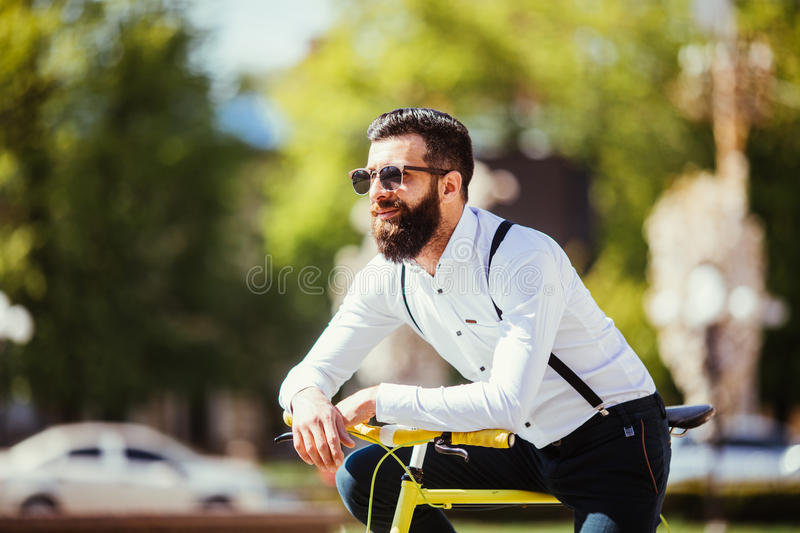 Young bearded man hipster in sunglasses leaning at his bicycle and looking away while standing on city street royalty free stock photography