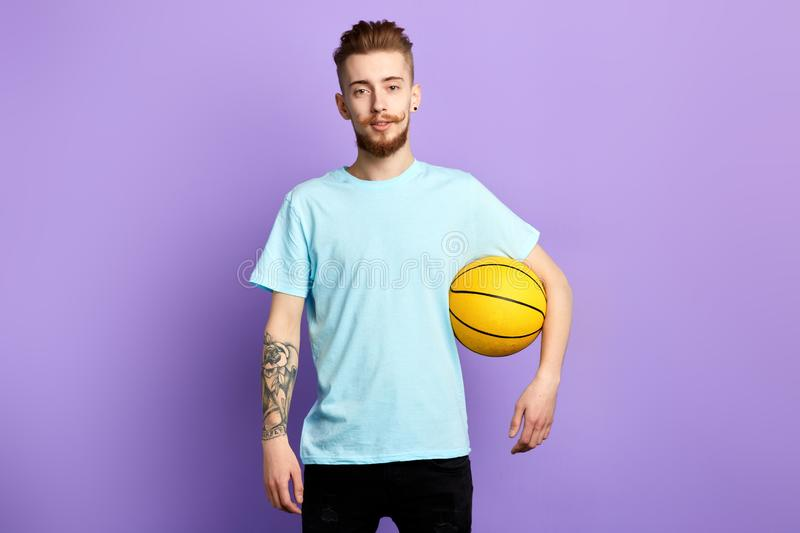 A young bearded man holding a basketball isolated on blue background. A young bearded man with tattoo holding a basketball isolated on blue background. lifestyle royalty free stock image
