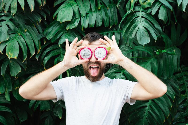 Young bearded man holding slices of Pitaya dragon fruit in front of his eyes, tongue out stock photo