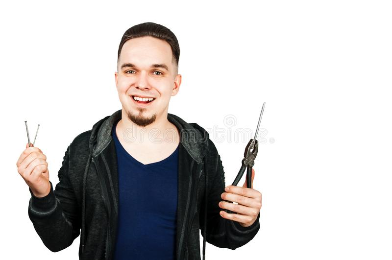 Young bearded man holds hobnail and pliers. Isolated on white background. Young bearded man holds hobnail and pliers. Isolated on a white background royalty free stock photography