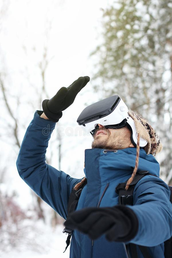 Young bearded man in knitted hat, warm jacket and gloves looks up using virtual virtual reality glasses in winter forest. Future. Technology concept. Copy space royalty free stock images