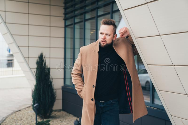 Young bearded man with modern hairstyle and trendy coat standing near business center royalty free stock photo