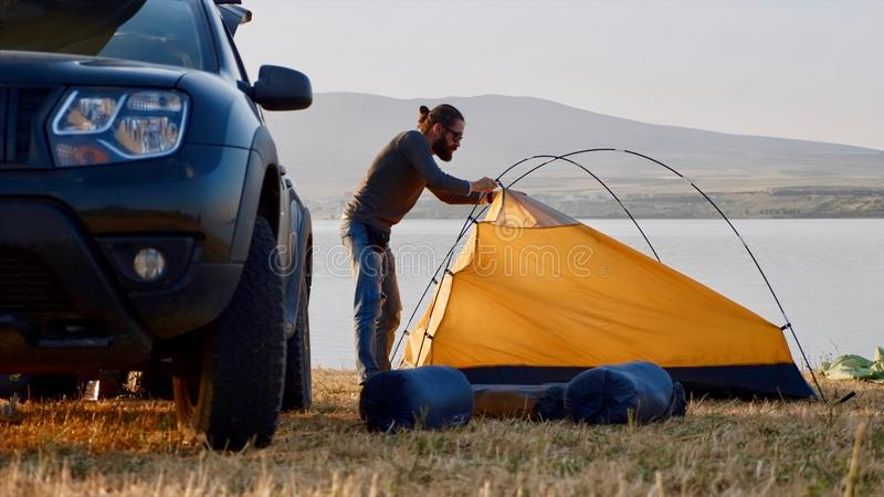 Young bearded man sets up a tent at campsite on the lake shore near his car. Traveler is came to the on his crossover and getting ready for the night royalty free stock images