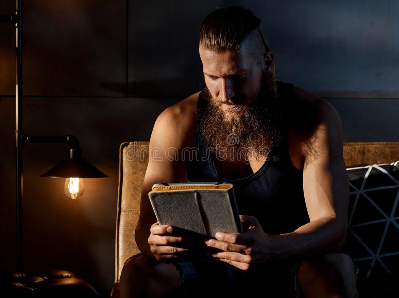 Young bearded man sitting in dark room with tablet stock photo
