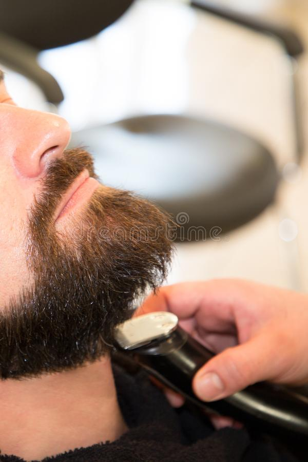 Bearded man sitting relaxed at barbershop by professional barber trimming beard stock photo