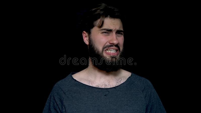 Young bearded man sniffing his armpit, something stinks very bad, isolated on black background. Negative emotion, facial royalty free stock photography