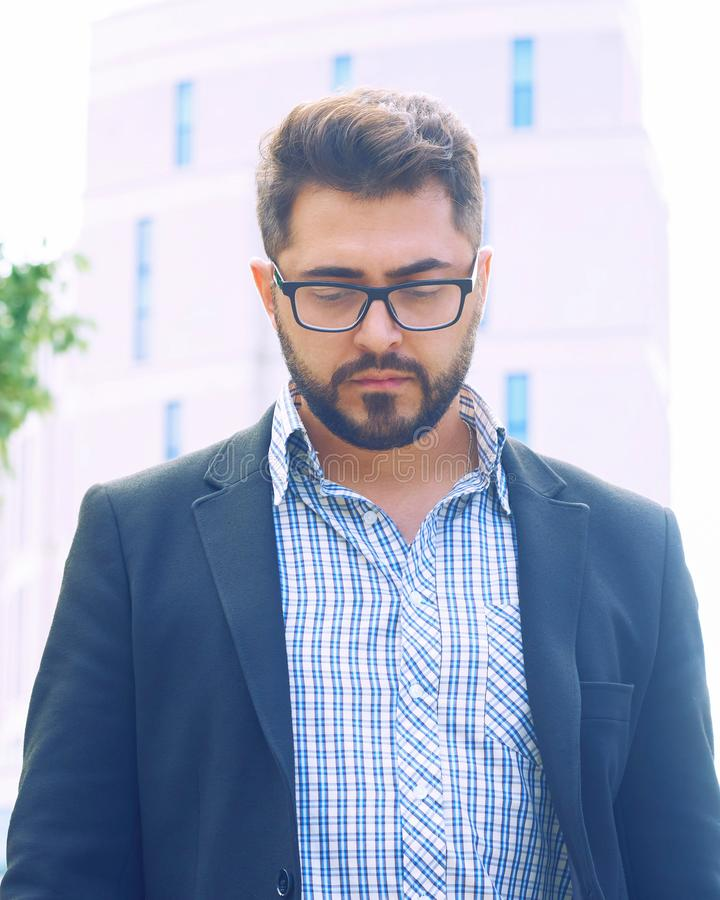 Young bearded man in spectacles thinking and looking down in the city outdoors. Portrait of the young bearded man in spectacles thinking and looking down in the royalty free stock photography