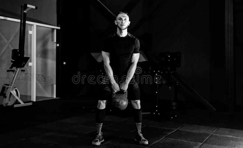 Young bearded man in sportswear working out with kettle bell. Gym. Kettlebell training in gym, muscle, body, healthy, exercise, lifestyle, fit, muscular royalty free stock image