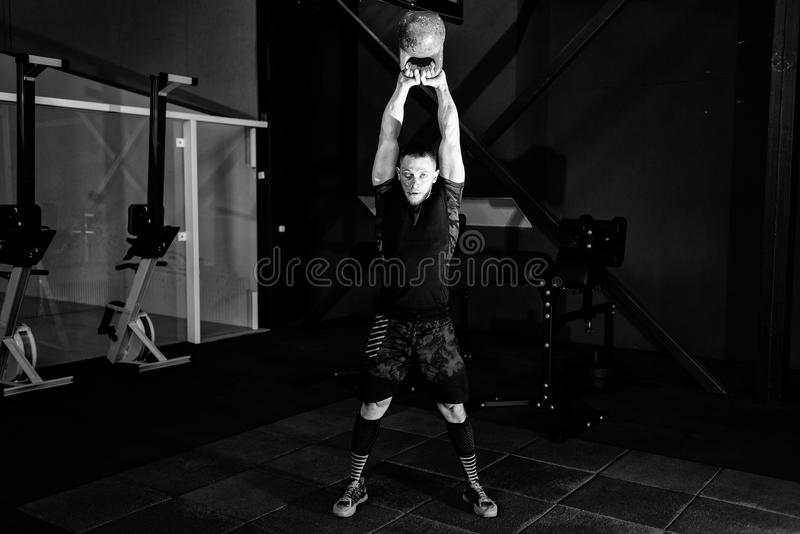Young bearded man in sportswear working out with kettle bell. Gym. Kettlebell training in gym, muscle, body, healthy, exercise, lifestyle, fit, muscular stock photography