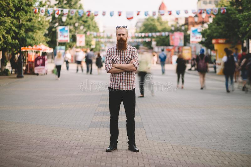 Young bearded man standing still at sidewalk in crowd traffic with people moving around stock images