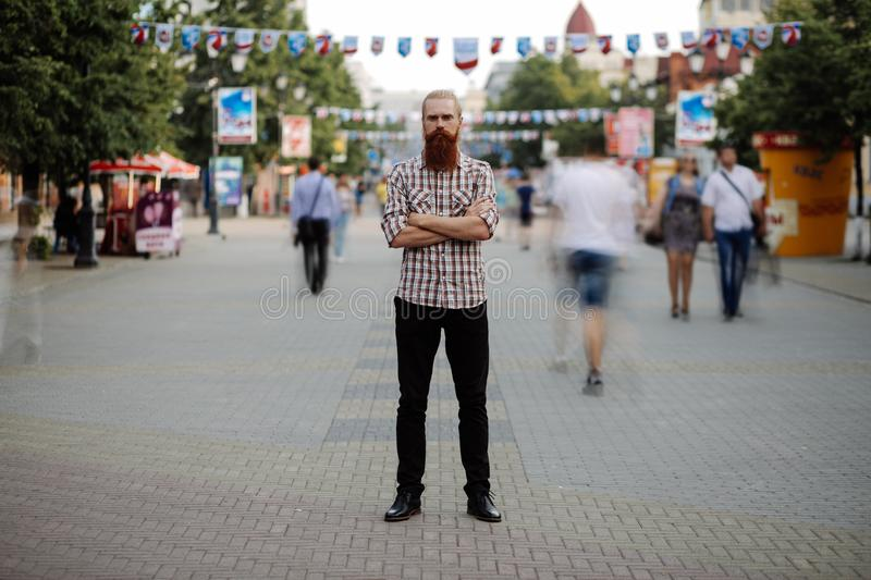Young bearded man standing still at sidewalk in crowd traffic with people moving around stock photography