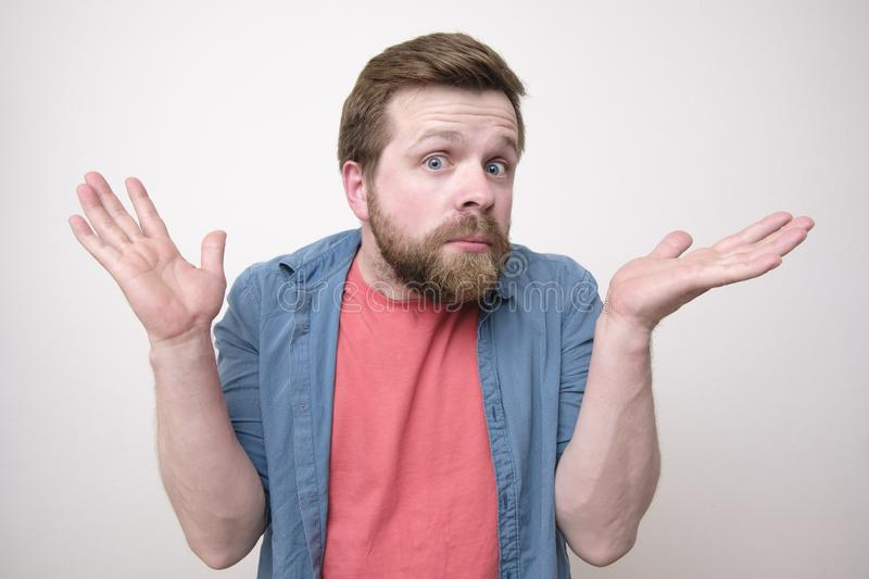 Young, bearded man is surprised and puzzled, and raises his hands in confusion. Isolated on white background royalty free stock photos