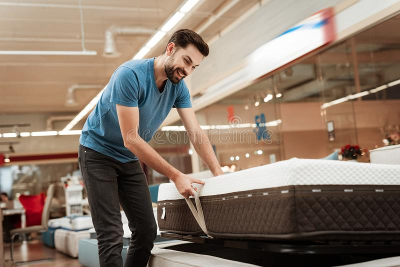 Young bearded man is testing mattress in furniture store. Orthopedic mattress for a healthy posture. Checking mattress in furniture store royalty free stock images