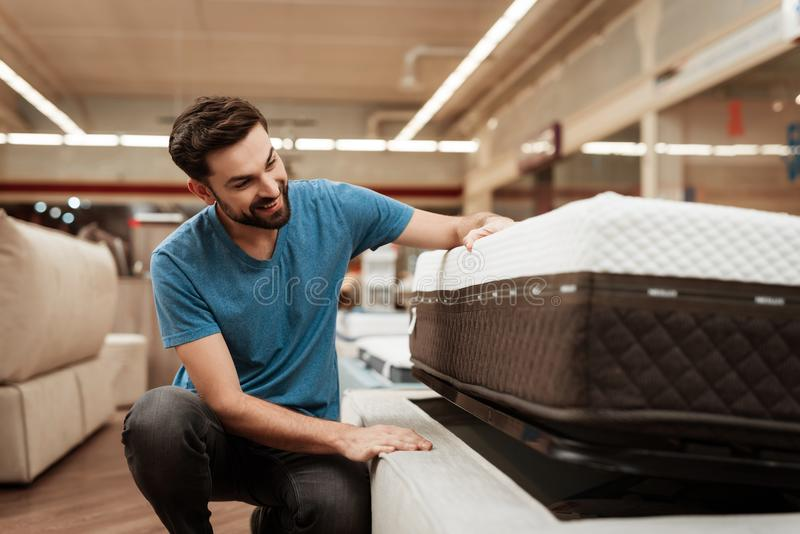 Young bearded man is testing mattress in furniture store. Orthopedic mattress for a healthy posture. Checking mattress in furniture store royalty free stock photo