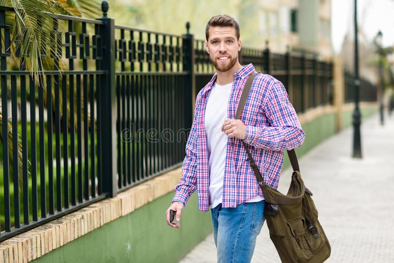 Young bearded man walking in urban background. Lifestyle concept. Young bearded man walking in urban background. Traveler wearing casual clothes. Lifestyle royalty free stock photos