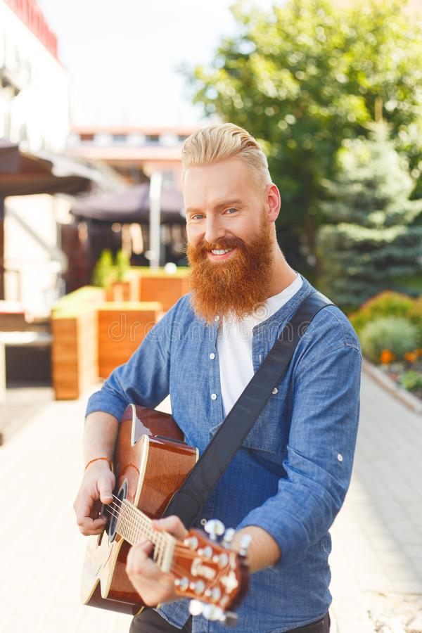 Young bearded man wearing blue Denim jacket, playing guitar outdoors.  royalty free stock images