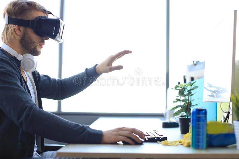 Young bearded man wearing virtual reality glasses in modern interior design coworking studio royalty free stock photography